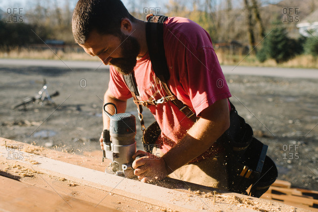 Man sanding a board for construction