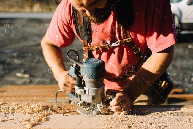 Man sanding wood for home building