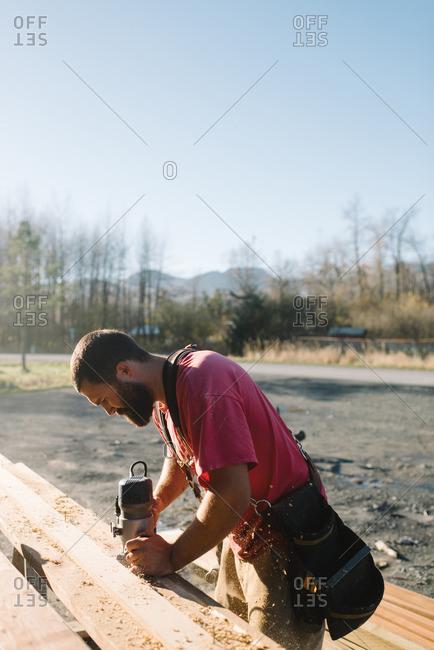 Man sanding wood for construction