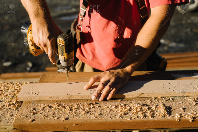 Man using a drill on a board