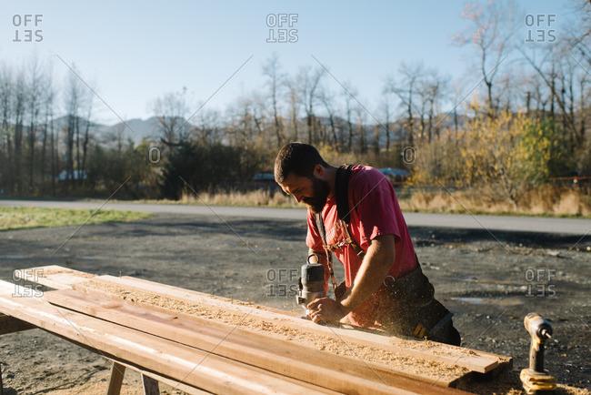 Man sanding down a wood board