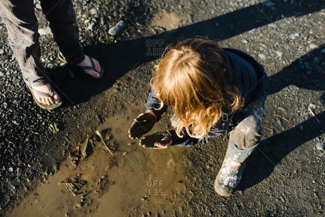 Girl looking at muddy hands