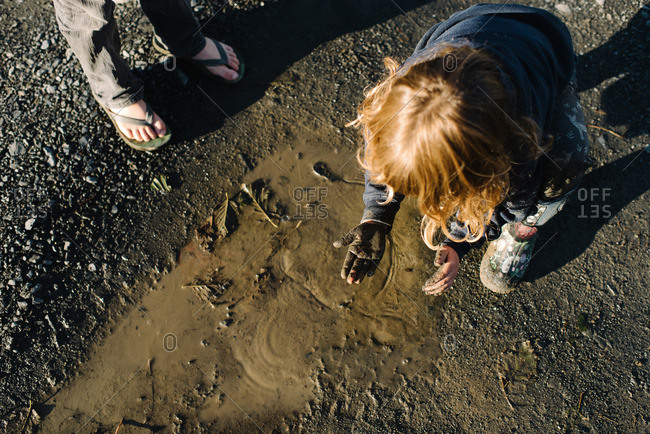 Girl looking at mud covered hands