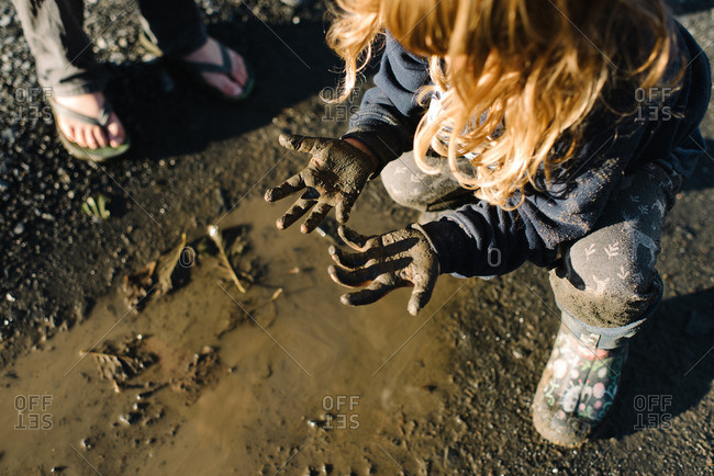 Girl looking at her muddy hands