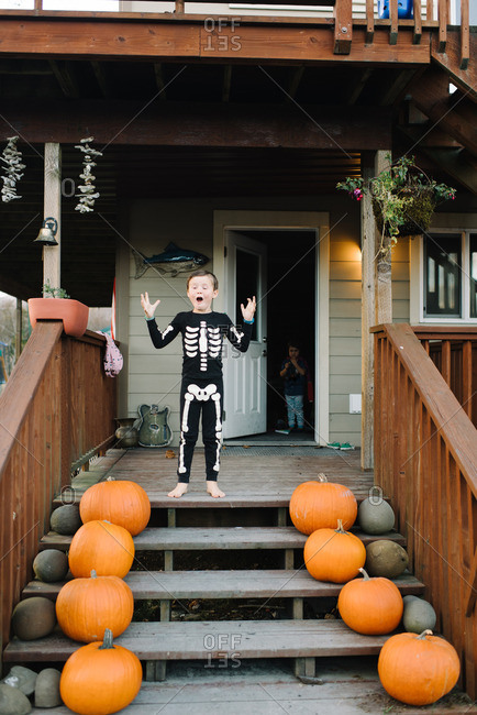 Boy in skeleton pajamas on porch