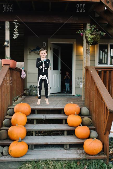 Boy jumping in skeleton pajamas on porch