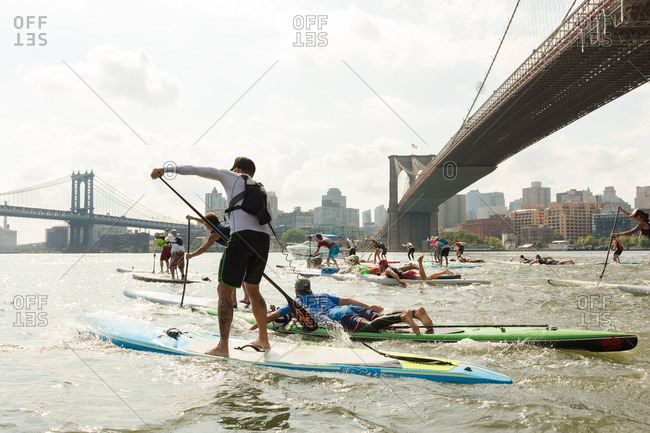 Manhattan, New York - August 20, 2016: People paddle boarding under the Brooklyn bridge during a competition