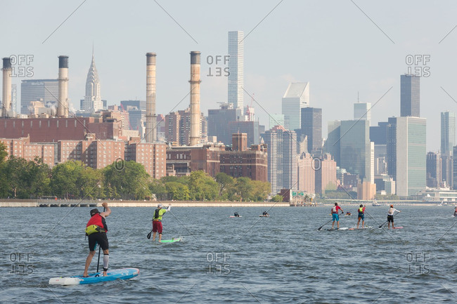 Manhattan, New York - August 20, 2016: People paddle boarding on the East river during a competition