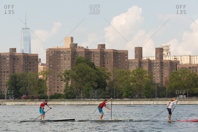 Manhattan, New York - August 20, 2016: Three men paddle boarding on the East river during a competition