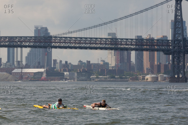 Manhattan, New York - August 20, 2016: Men paddle boarding under the Williamsburg bridge during a competition
