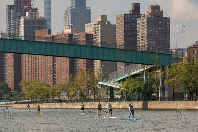 Manhattan, New York - August 20, 2016: People paddle boarding under the Ward's Island bridge during a competition