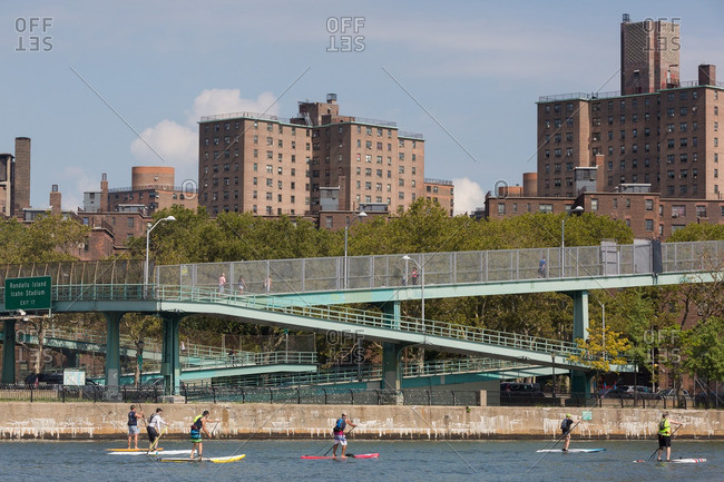 Manhattan, New York - August 20, 2016: People paddle boarding on the Harlem River during a competition