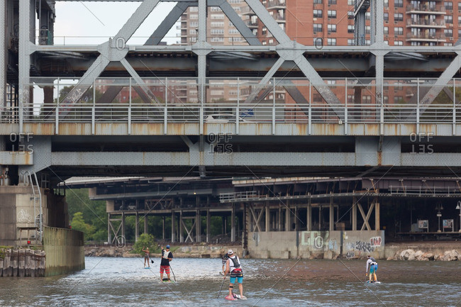 Manhattan, New York - August 20, 2016: Paddle boarders going under the Broadway bridge during a competition