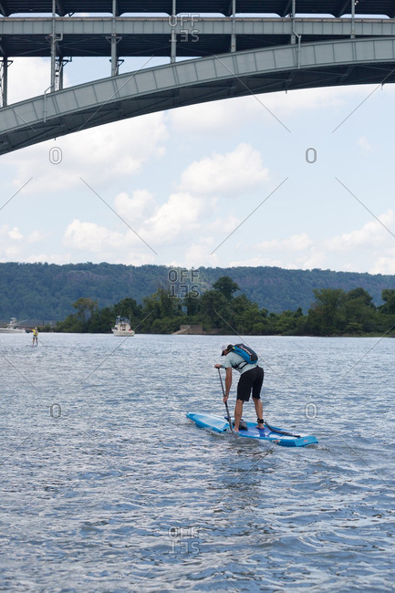 Manhattan, New York - August 20, 2016: Man paddle boarding under a the Henry Hudson bridge during a competition