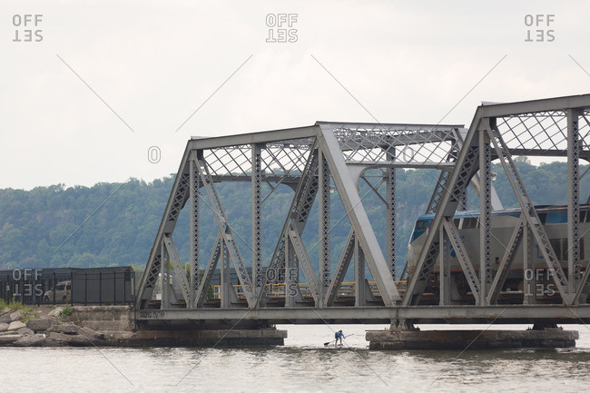 Manhattan, New York - August 20, 2016: Man paddle boarding under a the Spuyten Duyvil Bridge during a competition