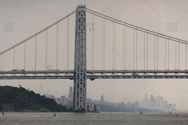 Manhattan, New York - August 20, 2016: Race contestants paddle boarding under the George Washington Bridge