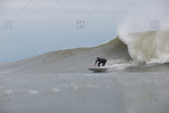 Man riding a rolling wave on a surfboard