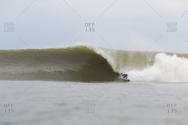 Man riding a large cresting wave on a surfboard