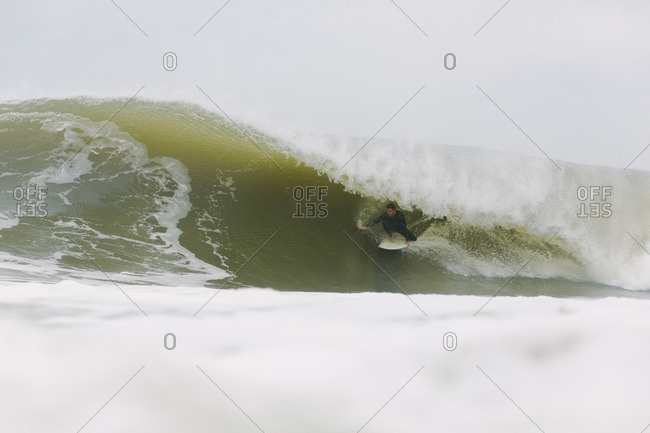 New York - September 5, 2016: Man riding in the barrel of a wave on a surfboard