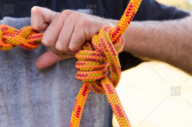 Man tying climbing ropes in a knot