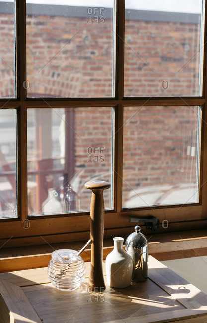 Pepper mill and honey jar on a window side table