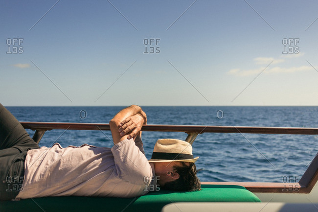 Man resting with hat on his face on a boat