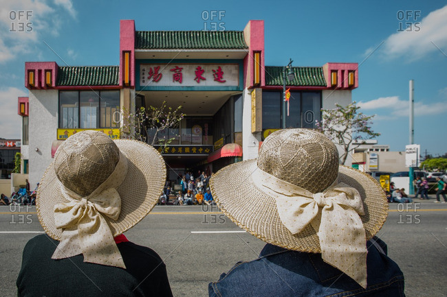 Chinatown, Los Angeles, California - 2/21/2015: Women wearing hats waiting for parade to start in Chinatown