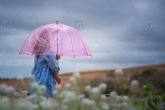 Girl walking with a pink see-through umbrella
