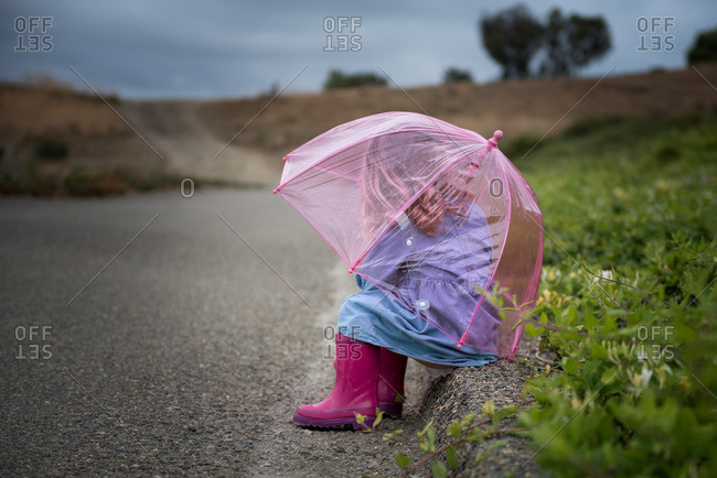 Girl sitting on a curb with a pink see-through umbrella