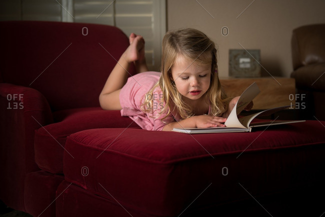 Little girl reading a book on a red chair