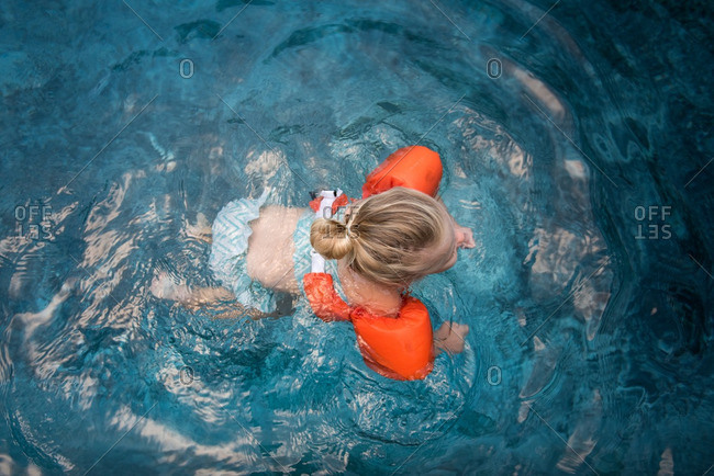 Girl swimming in a pool with an orange floatation device