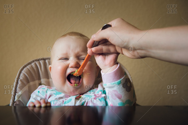 Baby eating green soft food