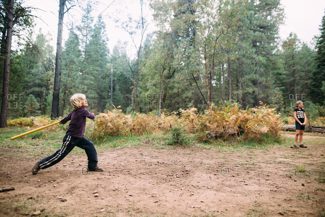 Boy playing baseball in forest