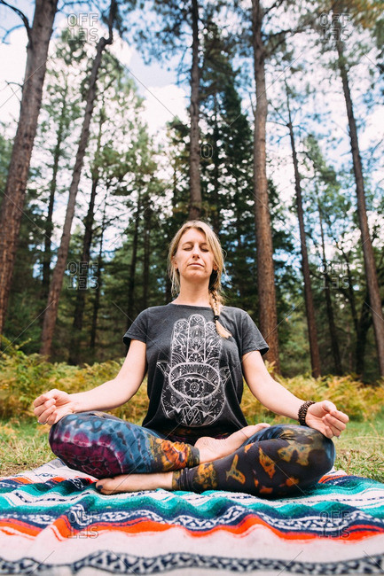 A woman meditating in a forest clearing