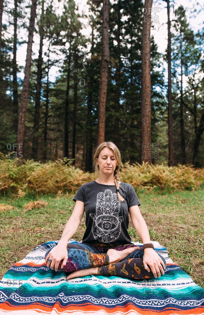 A woman meditating in forest clearing