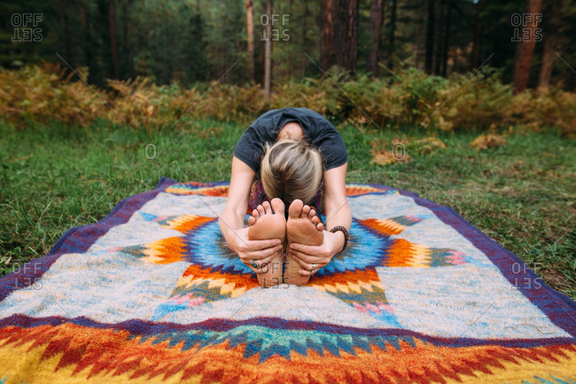 Woman stretching on blanket in woods