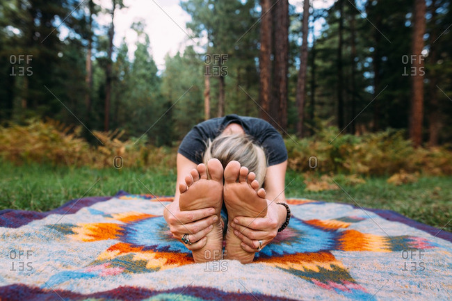 Woman in stretch on blanket in woods