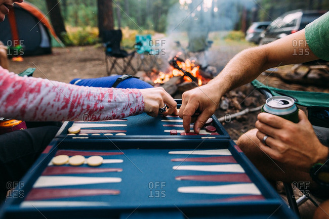Two people playing backgammon in campsite