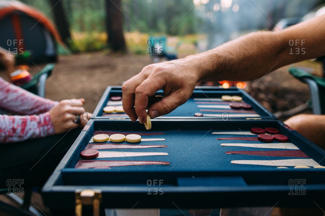 Two people playing backgammon while camping