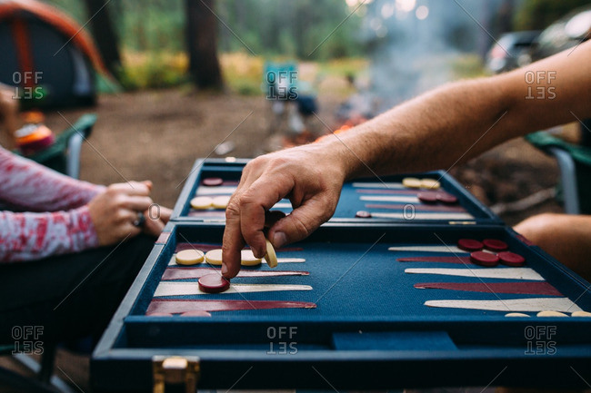 Two people playing backgammon at campsite