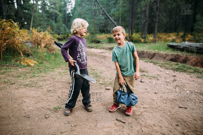 Boys in wooded setting with shovel