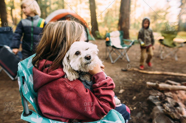 Girl hugging dog in campsite