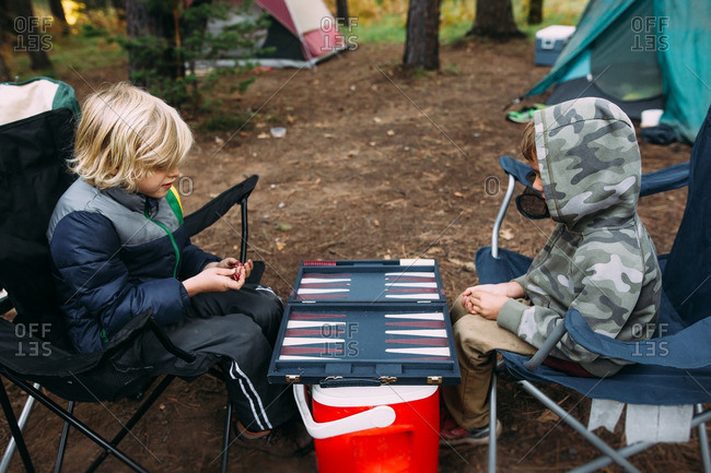 Boys playing backgammon in campsite