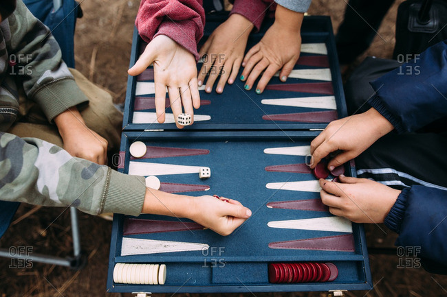 Kids playing backgammon together - Offset