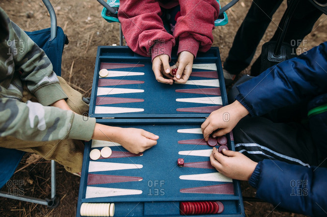 Hands of kids playing backgammon