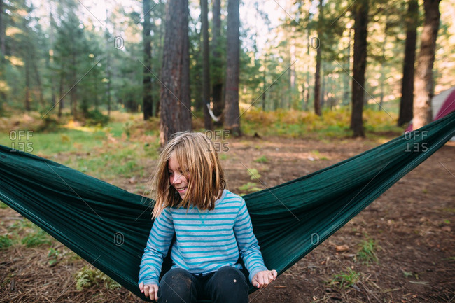 Girl smiling on hammock in woods
