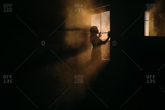 Woman by window in rays of sun