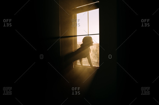 Woman looking out window in rays of sun