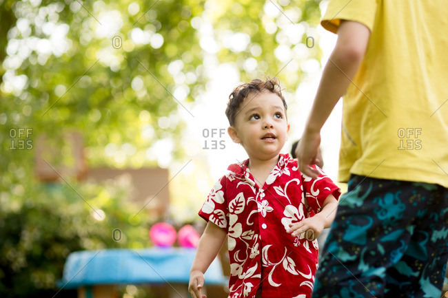 Boy in floral shirt looking up