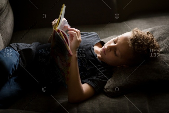Biracial boy reading on a couch
